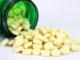 Vitamin B complex folic acid vitamins spilling from a green pill bottle.