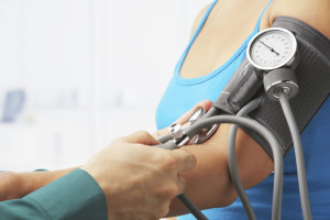 Checking blood pressure of female patient, unrecognizable people