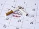 Broken cigarette lies on a calendar sheet. Tobacco wake. On the calendar inscription marker.